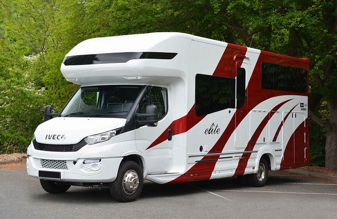 A red and white medium sized horsebox parked in a paddock