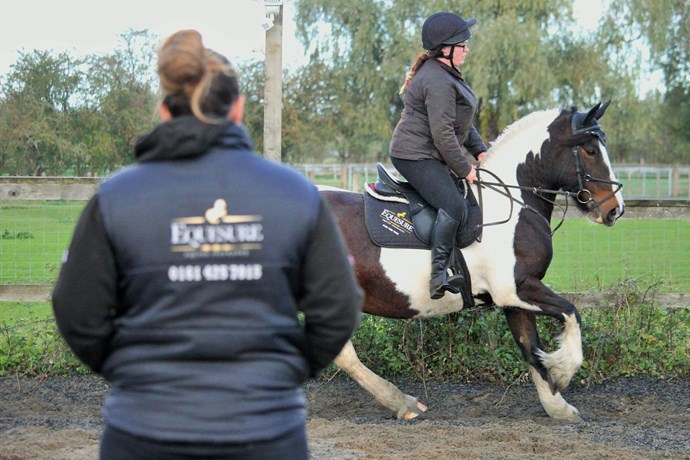 Teacher wearing Equesure clothing teaching a rider going around a paddock