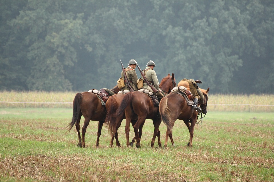Three horses carrying soldiers walking across a field