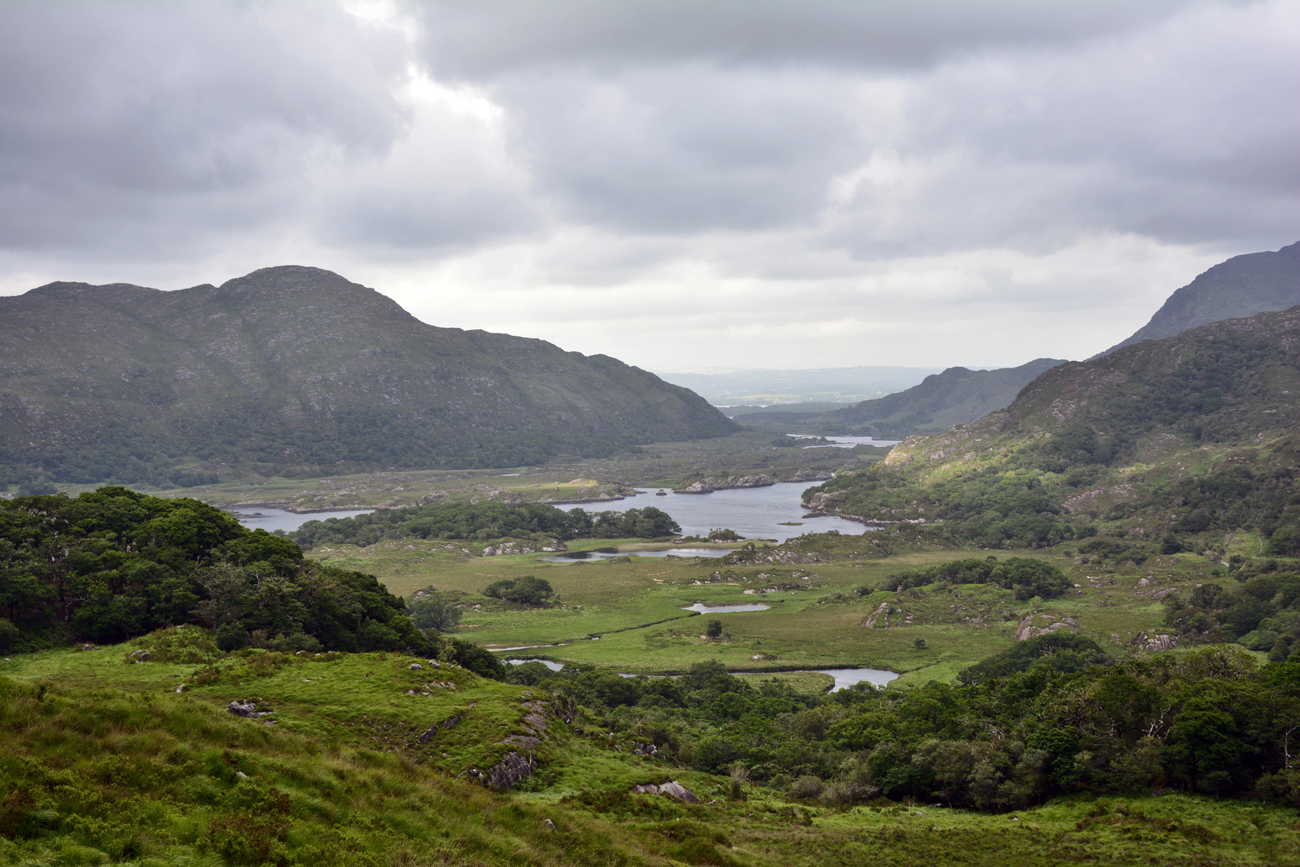 A vast view of low lying lakes and tall rocky hills in Ireland