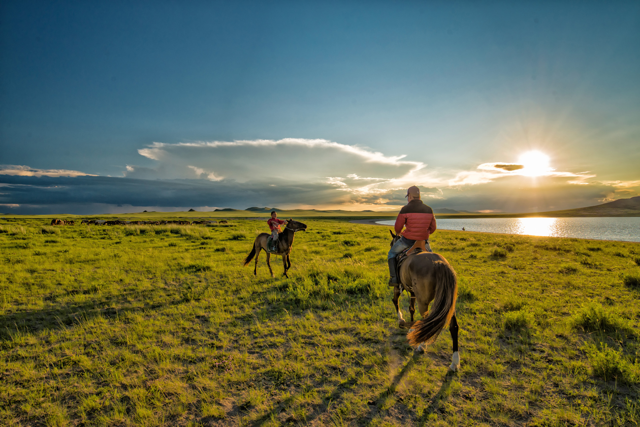 Two nomadic Mongolians riding their horses at sunset
