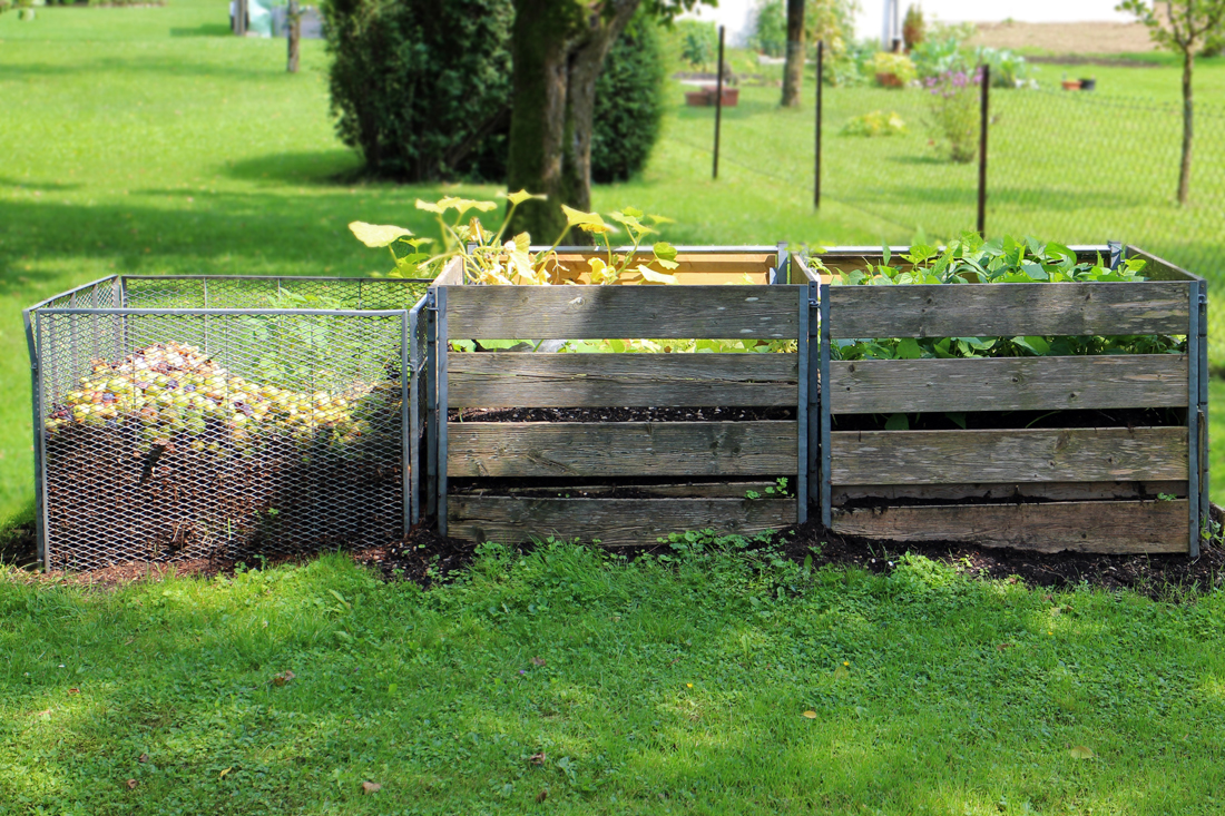 Three compost bins in a grassy field