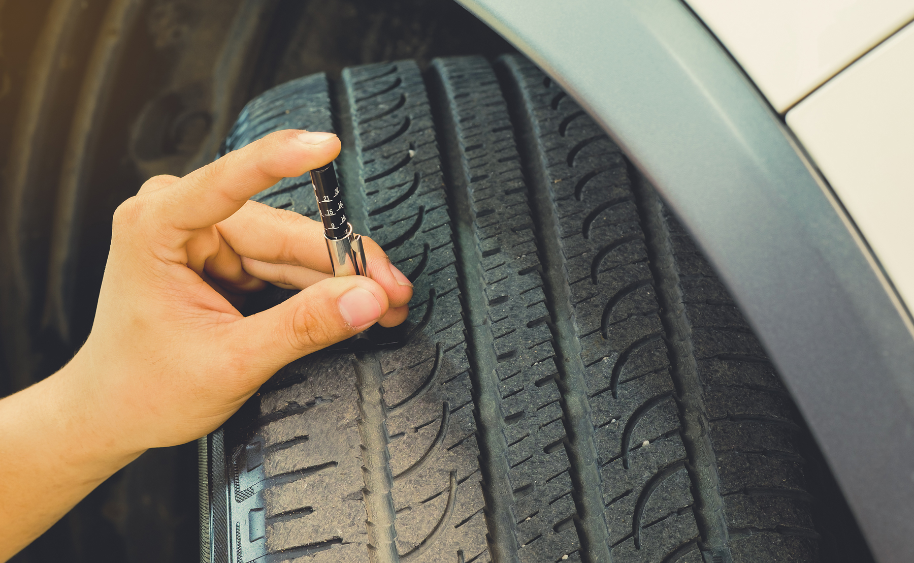 A person using a tool to check the tread depth of a tyre