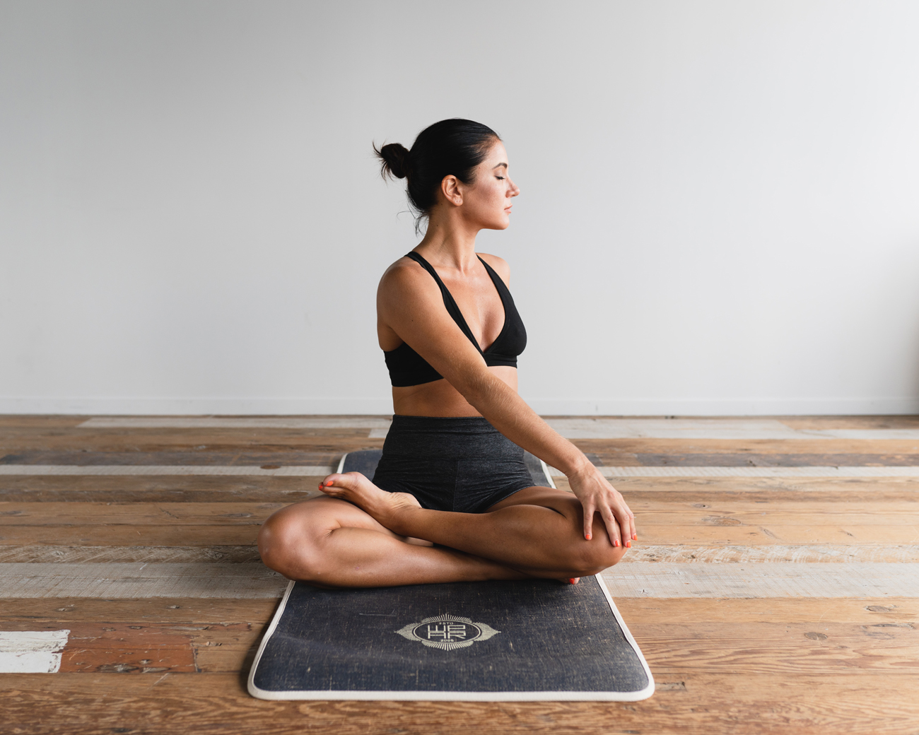 A woman sitting on a yoga mat doing a back stretch